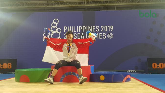 Lifter muda Indonesia, Rahmat Abdullah, berhasil meraih medali emas dalam debutnya di SEA Games 2019. (Bola.com/Zulfirdaus Harahap)