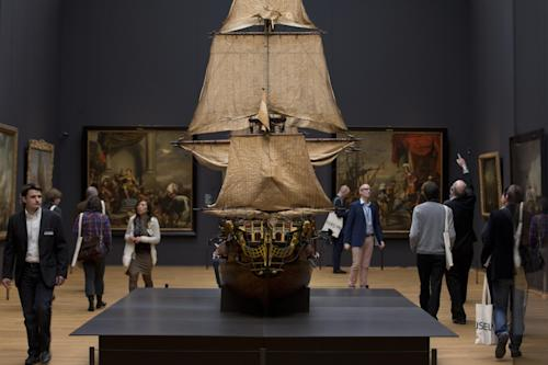 Visitors admire a 1698 model of the late 17th century Dutch warship William Rex during a press preview of the renovated Rijkmuseum in Amsterdam, Thursday, April 4, 2013. The Rijksmusuem, home of Rembrandt's Night Watch and other national treasures, is preparing to reopen its doors on April 13, 2013 after a decade-long renovation. (AP Photo/Peter Dejong)