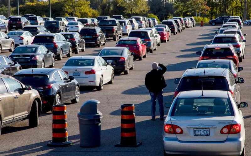 A man looks around as people wait in their cars at the Etobicoke General Hospital Drive-Thru coronavirus testing facility in Etobicoke, Ontario - Reuters