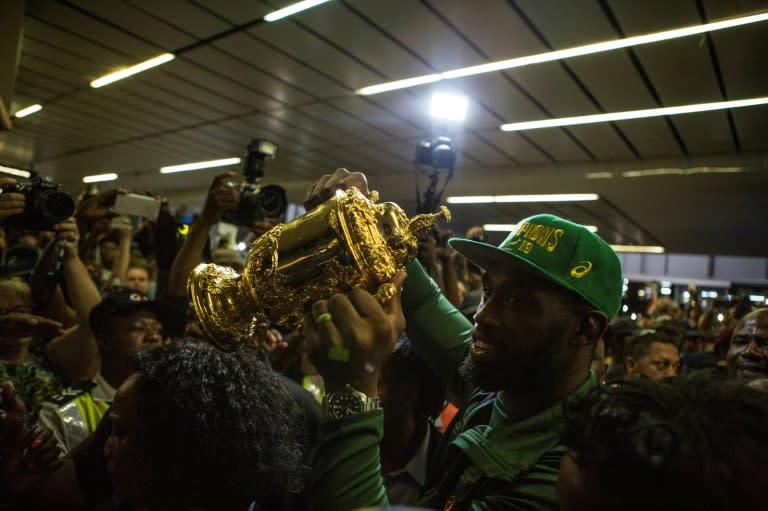 Springboks captain Siya Kolisi holds the William Webb Ellis trophy at OR Tambo airport near Johannesburg