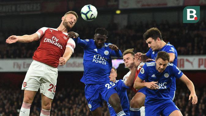Bek Arsenal, Shkodran Mustafi, duel udara dengan gelandang Leicester, Wilfred Ndidi, pada laga Premier League Inggris di Stadion Emirates, London, Senin (22/10). Arsenal menang 3-1 atas Leicester. (AFP/Glyn Kirk)