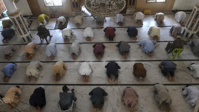 Umat muslim menerapkan jaga jarak aman atau physical distancing saat melaksanakan salat Jumat berjemaah selama Ramadan di sebuah masjid di Karachi, Pakistan, Jumat (1/5/2020). Umat muslim dunia melewati Ramadan tahun ini di tengah pandemi COVID-19. (Asif HASSAN/AFP)