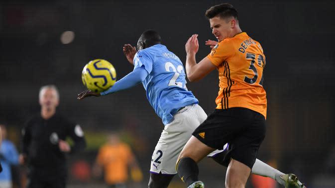 Gelandang Wolverhampton, Leander Dendoncker, duel udara dengan bek Manchester City, Benjamin Mendy, pada laga Premier League di Stadion Molineux,Wolves, Jumat (27/12). Wolves menang 3-2 atas City. (AFP/Paul Ellis)