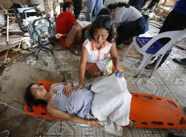 A woman comforts a pregnant relative having labour pains before she delivered a baby at a makeshift birthing clinic in typhoon battered Tacloban city