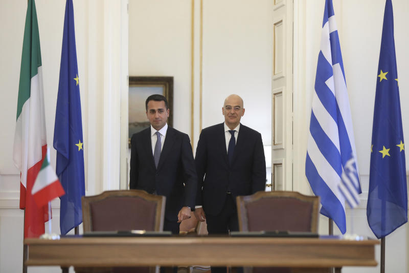 Greek Foreign Minister Nikos Dendias, right, and his Italian counterpart Luigi Di Maio arrive to sign an agreement following their meeting , in Athens, on Tuesday, June 9, 2020. Greece will lift all restrictions on Italian tourists entering the country gradually between June 15 and the end of the month, Greece's foreign minister said Tuesday.(Costas Baltas /Pool via AP)
