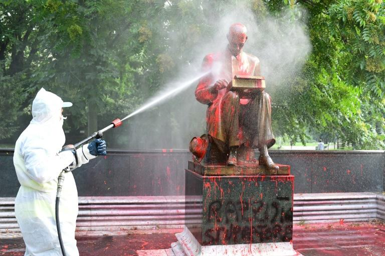 A city worker tries to spray clean the statue of Indro Montanell on Sunday morning after it was vandalised the night before