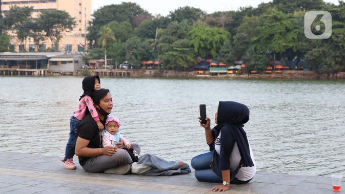Warga berfoto di area pedestrian Danau Sunter, Jakarta, Sabtu (27/6/2020). Beragam aktivitas dilakukan warga sambil menikmati waktu sore di area Danau Sunter, Jakarta. (Liputan6.com/Helmi Fithriansyah)