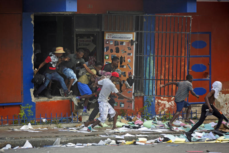 Looters run away from a store as national police arrive during a protest demanding the resignation of Haitian President Jovenel Moise in Port-au-Prince, Haiti, Feb. 12, 2019. The image was part of a series of photographs by Associated Press photographers which was named a finalist for the 2020 Pulitzer Prize for Breaking News Photography. (AP Photo/Dieu Nalio Chery)