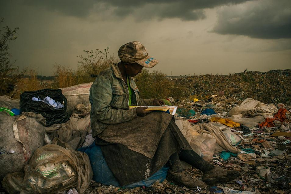 """In this photo provided on Friday Feb. 15, 2013 by World Press Photo, the 1st prize Contemporary Issues Single by Micah Albert, USA, for Redux Images, shows pausing in the rain, a woman working as a trash picker at the 30-acre dump, which literally spills into households of one million people living in nearby slums, wishes she had more time to look at the books she comes across. She even likes the industrial parts catalogs. """"It gives me something else to do in the day besides picking trash,"""" she said in Nairobi, Kenya, April 3, 2012. (AP Photo/Micah Albert, Redux Images)"""