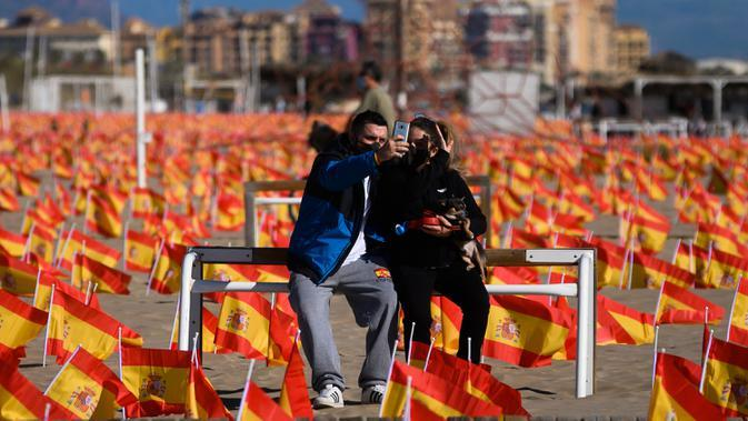Sepasang suami istri ber-wefie saat mereka duduk di antara ribuan bendera Spanyol yang mewakili korban COVID-19, di pantai Patacona, Valencia pada Minggu (4/10/2020). Virus corona di Spanyol sejauh ini telah merenggut lebih dari 32.000 nyawa dan 790.000 kasus terkonfirmasi. (Jose Jordan / AFP)