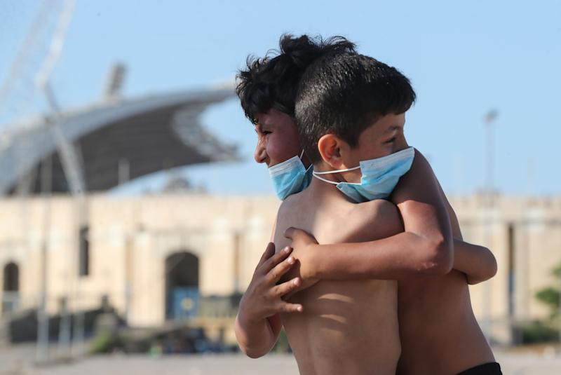 TOPSHOT - Mask-clad boys hug each other while playing football in front of the Camille Chamoun Sports City Stadium in the Lebanese capital Beirut amid the ongoing COVID-19 pandemic, on May 11, 2020. - Lebanon ordered a four-day-long lockdown to stem the spread of the coronavirus after recording an uptick in infections in recent days amid eased restrictions. (Photo by - / AFP) (Photo by -/AFP via Getty Images)