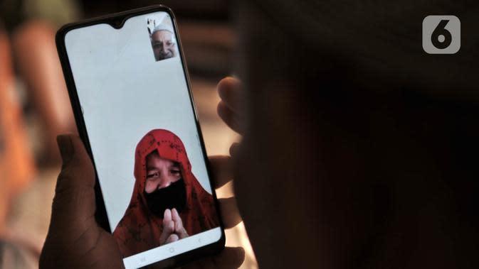Warga bermaaf-maafan dengan keluarga melalui panggilan video saat halalbihalal Idul Fitri di Jakarta, Minggu (24/5/2020). Halalbihalal virtual menjadi alternatif bersilaturahmi dengan keluarga di kampung halaman akibat tidak dapat mudik karena wabah virus COVID-19. (merdeka.com/Iqbal S. Nugroho)