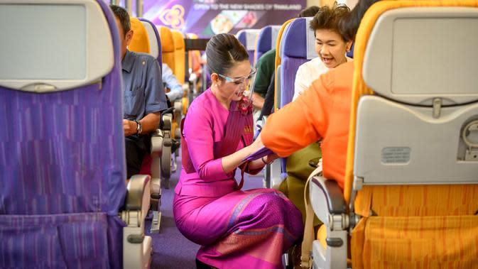 Seorang pramugari mengenakan pelindung wajah saat berbicara dengan pelanggan di restoran pop-up bertema kabin pesawat di kantor pusat Thai Airways di Bangkok, 10 September 2020. Di restoran ini para pengujung yang datang bisa merasakan kembali seluruh pengalaman penerbangan. (Mladen ANTONOV/AFP)