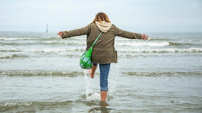 Seorang wanita menikmati suasana laut dan pantai di Dunkirk, Prancis (16/5/2020). Disertai langkah-langkah pencegahan seperti menjaga jarak sosial, sejumlah pantai di Prancis utara dibuka kembali mulai Sabtu (16/5) setelah pelonggaran lockdown akibat merebaknya COVID-19. (Xinhua/Sebastien Courdji)