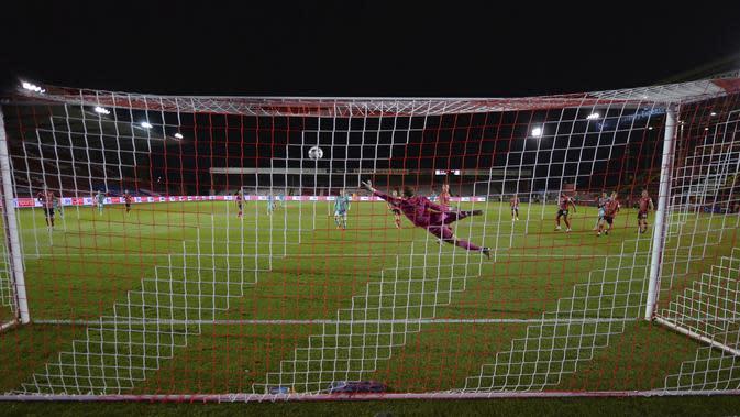 Kiper Lincoln City, Alex Palmer gagal menahan bola tembakan pemain Liverpool, Curtis Jones pada putaran ketiga Piala Liga Inggris di stadion LNER, Lincoln, Inggris, Kamis (24/9/2020). Liverpool menang telak 7-2 atas Lincoln City. (Peter Powell , Pool via AP)