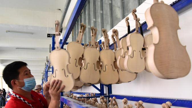 Pekerja menata biola di sebuah bengkel kerja di Queshan, Provinsi Henan, China, Rabu (20/5/2020). Kawasan industri penghasil alat musik tersebut mampu memproduksi 30.000 biola dan selo setiap tahun. (Xinhua/Zhu Xiang)