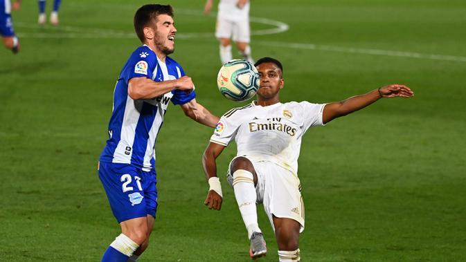 Penyerang Real Madrid, Rodrygo, berebut bola dengan bek Alaves, Martin Aguirregabiria, pada laga lanjutan La Liga pekan ke-35 di Stadion Alfredo di Stefano, Sabtu (11/7/2020) dini hari WIB. Real Madrid menang 2-0 atas Alaves. (AFP/Gabriel Bouys)