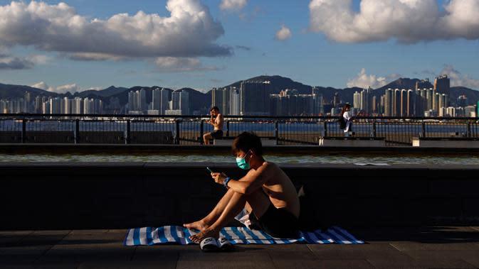 Seorang pria yang mengenakan masker duduk berjemur di sebuah taman di Hong Kong, Rabu (22/7/2020). Hong Kong menghadapi