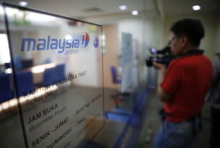 A journalist films the Malaysia Airlines ticket office in Jakarta