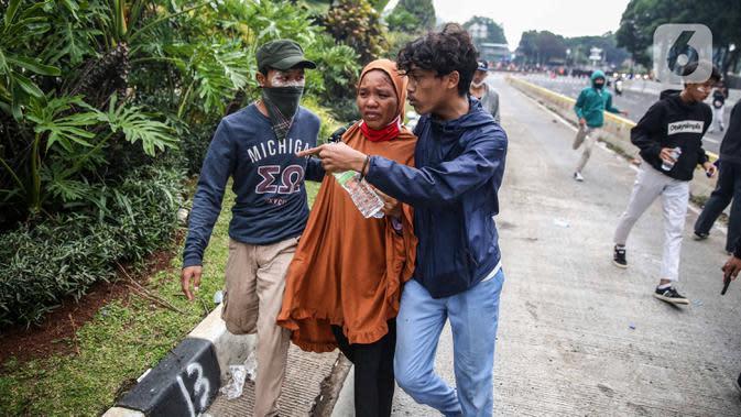 Seorang perempuan diselamatkan pendemo saat pengunjuk rasa terlibat bentrok dengan polisi di kawasan Patung Kuda, Jakarta, Selasa (13/10/2020). Perempuan tersebut terjebak saat unjuk rasa menolak Omnibus Law Undang-Undang Cipta Kerja ricuh. (Liputan6.com/Faizal Fanani)