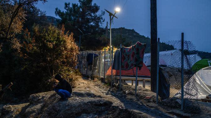 Seorang imigran berbicara di telepon genggamnya di luar kamp pengungsi di pulau Samos, Yunani (13/11/2019). Kamp Samos, awalnya dibangun untuk menampung 650 orang, telah lama melampaui batas-batasnya. (AFP Photo/Angelos Tzortzinis)