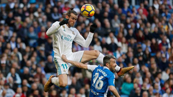 Pemain Real Madrid, Gareth Bale melompat untuk merebut bola dari pemain Deportivo La Coruna, Luisinho dalam lanjutan La Liga Spanyol di Santiago Bernabue, Senin (22/1). Real Madrid pesta kemenangan 7-1 atas Deportivo La Coruna. (AP/Francisco Seco)