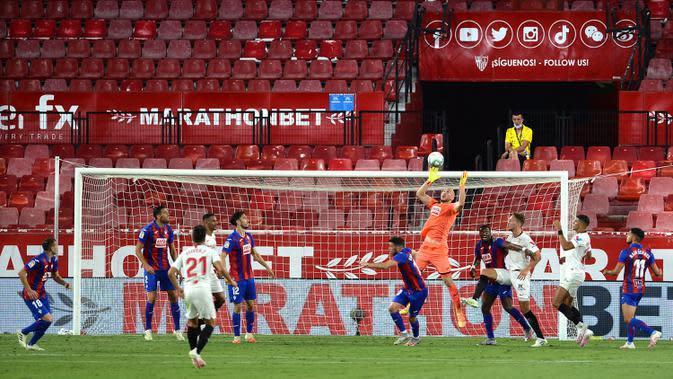 Kiper Eibar, Marko Dmitrovic, berusaha menangkap bola saat menghadapi Sevilla pada laga lanjutan La Liga pekan ke-34 di Estadio Ramon Sanchez Pizjuan, Selasa (7/7/2020) dini hari WIB. Sevilla menang 1-0 atas Eibar. (AFP/Cristina Quicler)