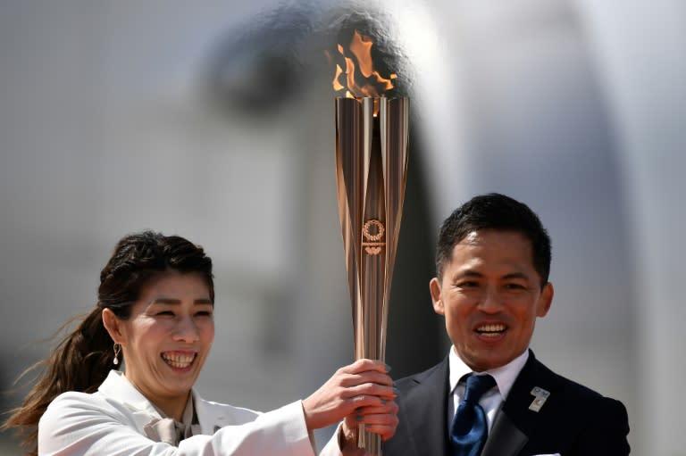Japanese Olympic gold medallists Saori Yoshida (L) and Tadahiro Nomura lit a Tokyo 2020 cauldron with the ceremonial flame