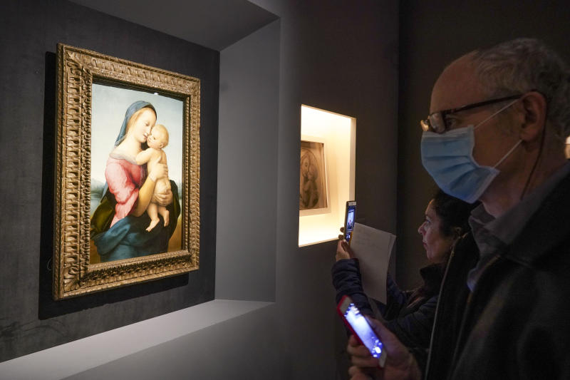 A man  looks at Raphael's oil on wood panel, Madonna con il Bambino (Virgin with the Child), in Rome, Wednesday, March 4, 2020. The paintings,  drawings and sketches in the most ambitious assemblage ever of Raphael works in an exhibition, more than even the Renaissance superstar had in his workshop at one time, are collectively insured for 4 billion euros ($.4 billion), against the likes of theft or vandalism. But no money can guarantee that Italy's outbreak of coronavirus, the largest in Europe, won't play havoc with the three-month run in Rome of the art world's eagerly-awaited blockbuster. (AP Photo/Andrew Medichini)