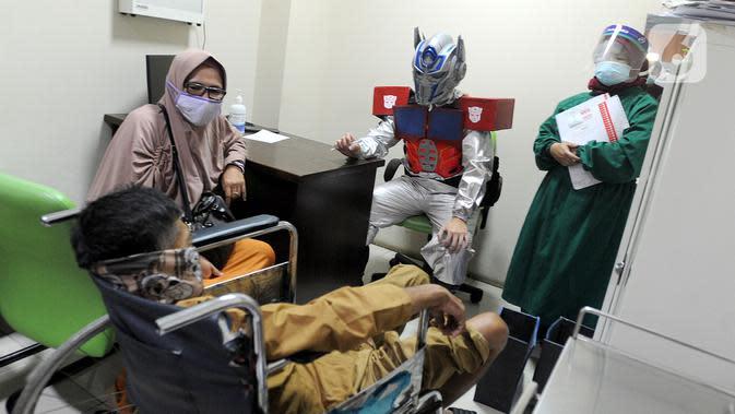 APD TRANSFORMERS: Dokter Rollando Erric Manibuy SpOT mengenakan APD ala transformers saat melayani pasiennya di RS Vania, Bogor, Jawa Barat, Jumat (22/5/2020). Penggunaan APD unik sejak merebaknya COVID-19 tersebut agar pasien tetap optimis meski sedang dalam pandemi. (merdeka.com/Arie Basuki)