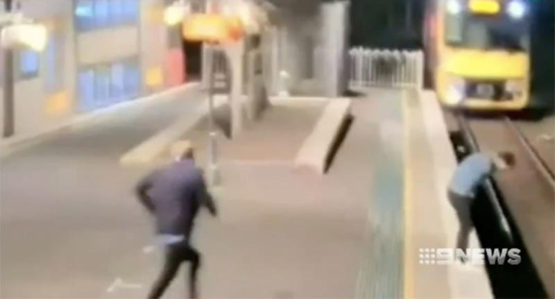 A man runs toward a commuter feeling unwell on the edge of the platform as a train approaches on a Sydney train station. Source: 9 News