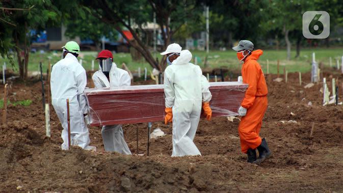 Petugas menggotong peti jenazah pasien Covid-19 di TPU Tegal Alur, Jakarta, Rabu (15/4/2020). Juru bicara pemerintah untuk penanganan virus corona Achmad Yurianto menyampaikan per Rabu (15/4) jumlah pasien terkonfirmasi 5.136 dan meninggal 469 orang. (Liputan6.com/Helmi Fithriansyah)