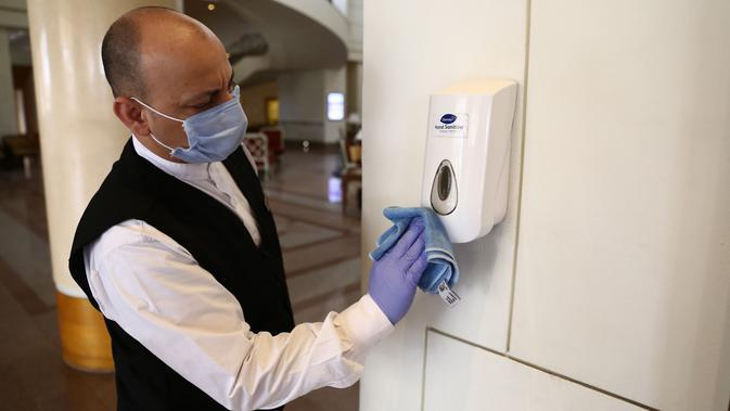 Seorang karyawan hotel membersihkan dispenser cairan pembersih tangan di Hotel Conrad di Kairo, Mesir pada Selasa (2/6/2020). Pemerintah Mesir mulai mengizinkan puluhan hotel beroperasi kembali untuk melayani wisatawan lokal dengan kapasitas dibatasi 50 persen. (Xinhua/Ahmed Gomaa)
