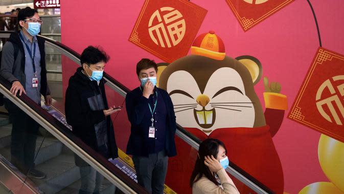 Orang-orang memakai masker saat menaiki eskalator di Bandara Internasional Hong Kong di Hong Kong, Selasa (21/1/2020). Masker terjual habis dan pemeriksaan suhu di bandara dan stasiun kereta api menjadi norma baru di China menyusul merebaknya wabah virus corona. (AP/Ng Han Guan)