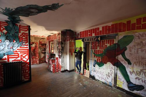 A visitor takes pictures in a social housing tower converted into a temporary street art exhibition in Paris, France, Tuesday, Oct. 8, 2013. Condemned apartments never looked so good _ and only rarely has graffiti met such an enthusiastic welcome. More than 80 artists were given free run of a rundown building that is doomed to destruction in 8 days. The line wraps around the block every day to see the apartments, each of which is its own art installation. (AP Photo/Francois Mori)