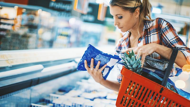 Woman looks at bag of frozen food
