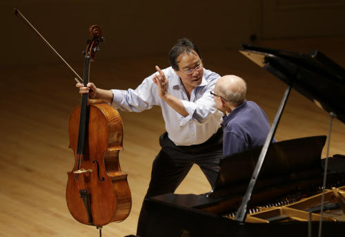 Cellist Yo-Yo Ma, left, rehearses with Holocaust survivor George Horner on stage at Symphony Hall Tuesday afternoon, Oct. 22, 2013, in Boston. The 90-year-old pianist will make his orchestral debut with Ma Tuesday night, where they will play music composed 70 years ago at the Nazi prison camp where Horner was imprisoned. (AP Photo/Steven Senne)