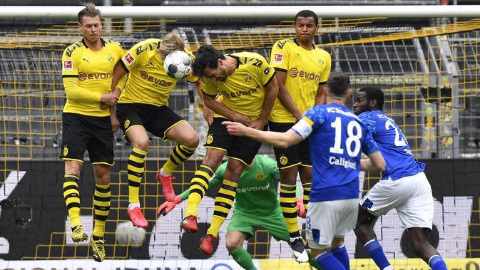 Para pemain Borussia Dortmund berusaha menghadang tendangan pemain Schalke 04, Daniel Caligiuri, pada laga Bundesliga di Stadion Signal Iduna Park, Sabtu (16/5/2020). Dortmund menang 4-0 atas Schalke 04. (AP/Martin Meissner)