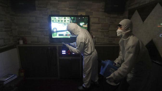 Petugas mengenakan pakaian pelindung menyemprotkan Disinfektan untuk mencegah penyebaran virus corona Covid-19 di Karaoke di Seoul, Korea Selatan, (13/3/2020). Penyemprotan disinfektan terus dilakukan di setiap sudut tempat di Korsel. Salah satunya sampai ke tempat karaoke. (AP Photo/Ahn Young-joon)