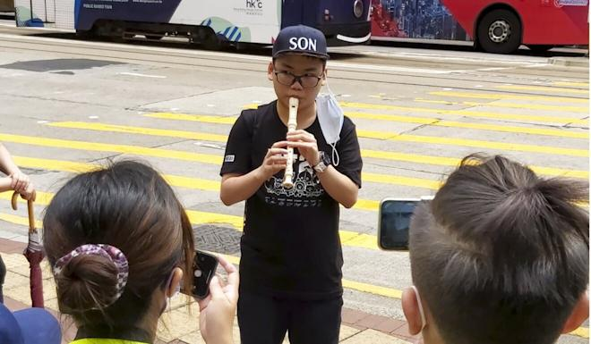 Student Max Jin plays his recorder in Causeway Bay. Photo: Jack Lau