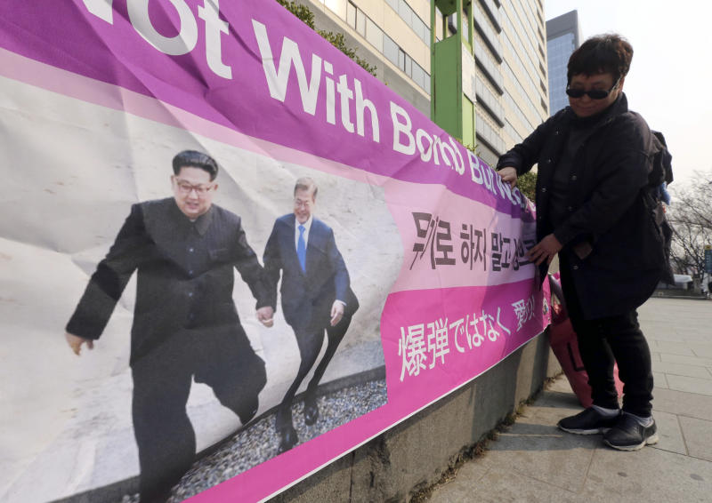 """A woman displays a banner showing a photo of North Korean leader Kim Jong Un and South Korean President Moon Jae-in, right, to wish for peace on the Korean Peninsula, in Seoul, South Korea, Tuesday, March 19, 2019. International journalists' organizations have expressed concern over South Korea's press freedoms after the country's ruling party singled out a Bloomberg reporter over what it claimed was a """"borderline treacherous"""" article insulting Moon, resulting in threats to the reporter's safety. (AP Photo/Ahn Young-joon)"""