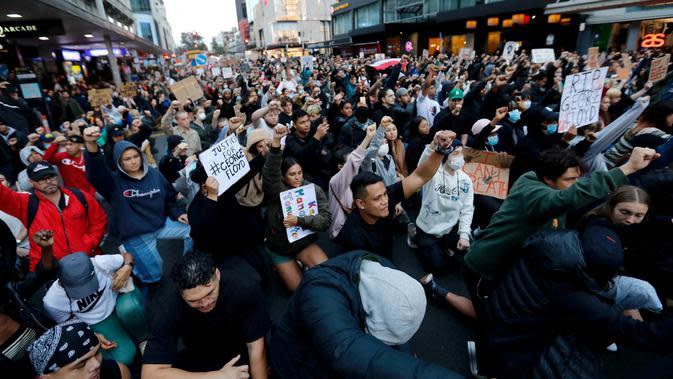 Demonstran memegang plakat saat memprotes kematian George Floyd di pusat Auckland, Selandia Baru, Senin (1/6/2020). Kematian pria kulit hitam George Floyd saat ditangkap oleh polisi Amerika Serikat memicu kemarahan di sejumlah negara. (Dean Purcell/New Zealand Herald via AP)