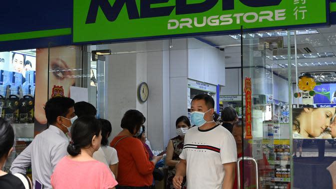 Warga mengantre di luar apotek untuk membeli masker, termometer, dan pembersih tangan di Singapura (29/1/2020). Singapura sejauh ini mengonfirmasi tujuh kasus virus corona - semuanya datang dari Wuhan. (AFP Photo/Roslan Rahman)