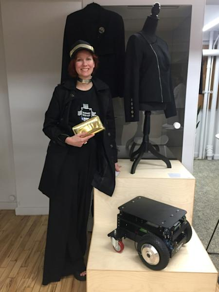 Anina Trepte, a former model and founder of the 360Fashion Network, poses next to one of her creations: a robot that can serve drinks and is activated by wearable technology hidden in a jacket