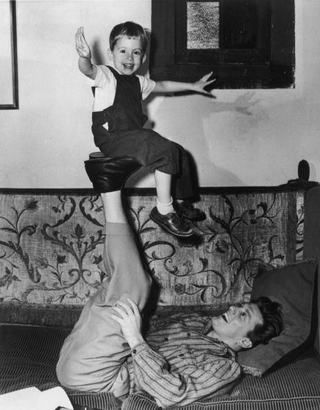 <p>Kirk plays with his son Michael by balancing him on the soles of his feet.  </p>