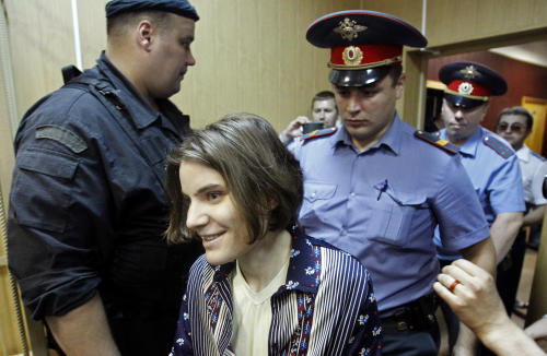 "Yekaterina Samutsevich, a member of the feminist punk band, Pussy Riot, is escorted in a district court in Moscow, Wednesday, June 20, 2012. She and two other band members face up to seven years on hooliganism charges after their February ""punk prayer"" at Moscow's Christ the Savior Cathedral in which they asked Holy Mary to deliver Russia from President Vladimir Putin.(AP Photo/Misha Japaridze)"