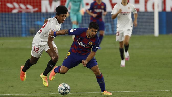 Striker Barcelona, Luis Suarez, berebut bola dengan pemain Sevilla, Jules Kounde, dalam laga lanjutan La Liga Spanyol, Sabtu (20/6/2020) dini hari WIB. Barcelona bermain imbang 0-0 atas Sevilla. (AP/Angel Fernandez)