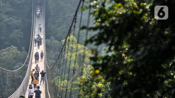 Pengunjung melintasi Jembatan Gantung Situ Gunung di Sukabumi, Minggu (20/9/2020). Seperti diketahui, Jembatan Gantung tersebut resmi dibuka untuk umum pada 2018 lalu itu memiliki panjang 243 meter dengan lebar 1,2 meter dan berada di atas ketinggian 107 meter. (merdeka.com/Iqbal S. Nugroho)