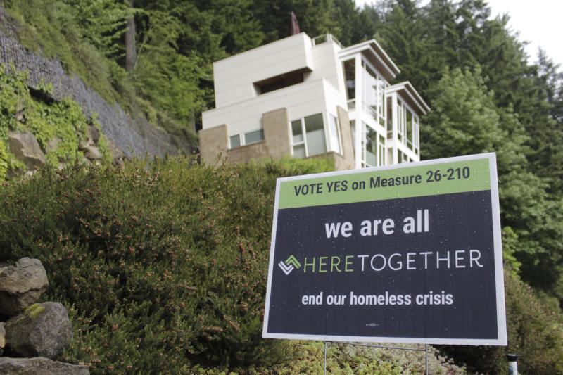 "FILE - In this May 14, 2020, file photo, a campaign sign urging people to vote ""Yes"" on Measure 26-210, which would approve taxes on personal income and business profits to raise $2.5 billion over a decade to fight homelessness, is displayed near an upscale home in Portland, Ore. A measure to tax the incomes of the wealthiest residents and the profits of the biggest businesses to raise $2.5 billion over a decade to address the homeless crisis sailed to victory in the Portland, Oregon metropolitan region even as the state faces crippling revenue losses and record-high unemployment. Nearly 60% of voters in the three counties that make up the greater Portland region approved the tax amid a greatest economic turmoil in years, a sign of just how intractable the homeless problem has become in the liberal Pacific Northwest city. (AP Photo/Gillian Flaccus, File)"