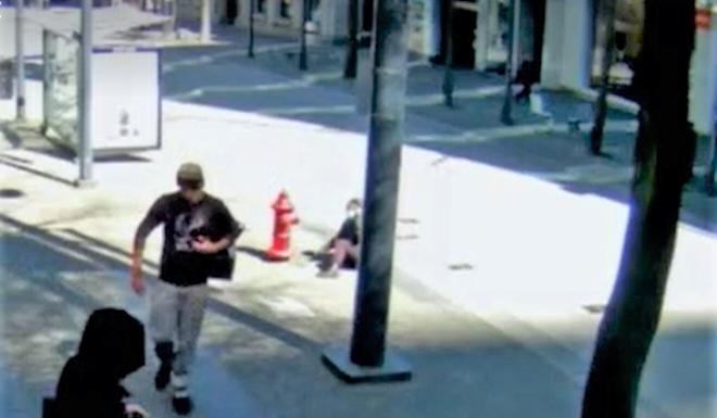 A 22-year-old Asian woman wearing a blue face mask, on ground near fire hydrant, watches her attacker walk away after she was punched on April 12 in Vancouver. Photo: Vancouver Police Department